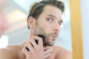 Man in front of mirror using electronic shaver @Goodluz
