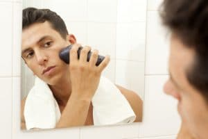 Young man shaving with electric shaver at the bathroom @cristovao